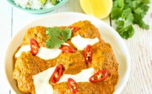 A zoomed in picture of a bowl of beef kofta curry garnished with yoghurt and sliced chilli