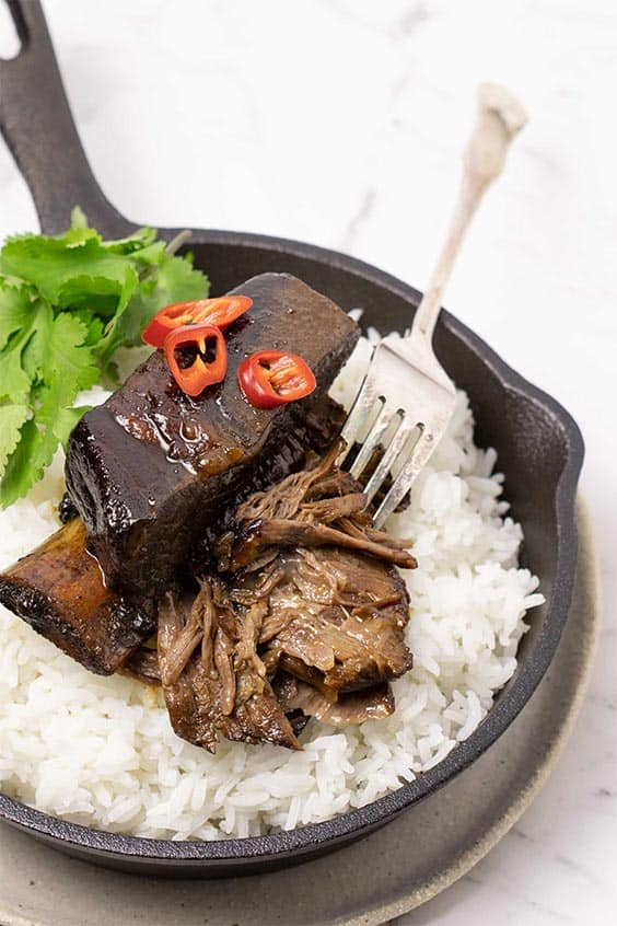 A saucepan with fluffy rice and sticky Asian beef ribs garnished with fresh chilli slices and cilantro