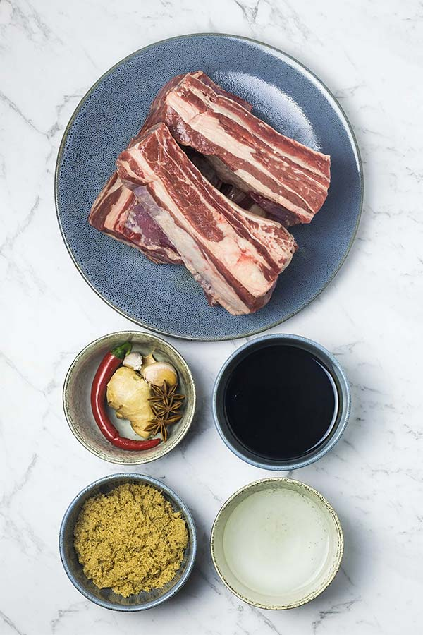 Beef ribs, dark soy sauce, water, brown sugar and a few aromatics in individual bowls on a marble counter top