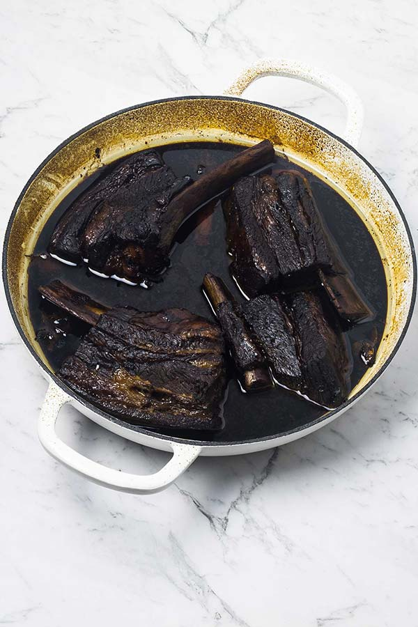 Steam oven baked sticky Asian beef ribs in a dark sauce in a white casserole dish