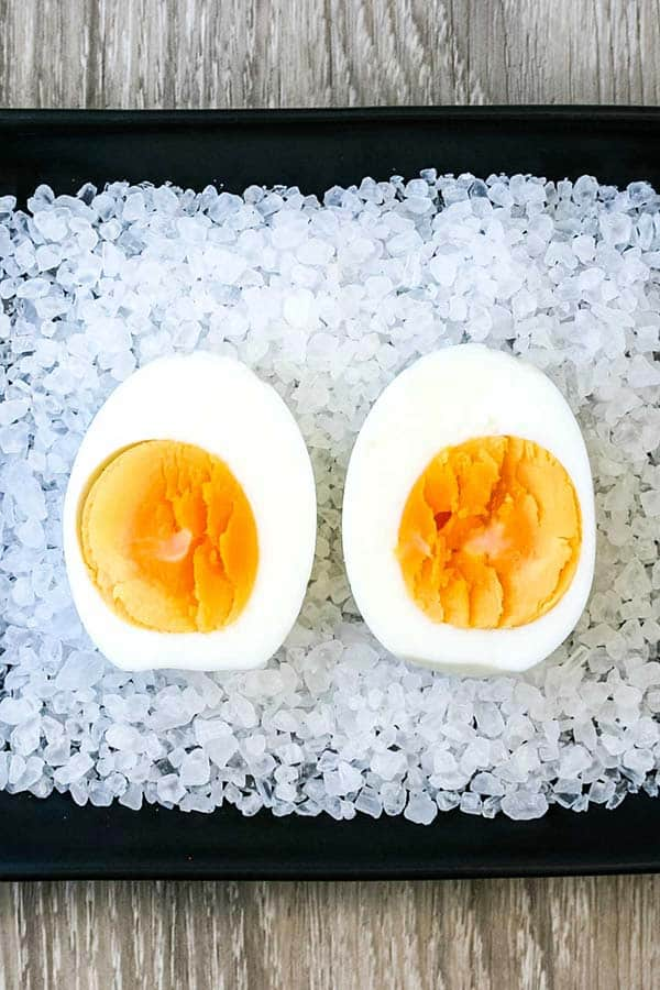 A halved boiled egg, with a mostly hard yolk, on a bed of rock salt on a black serving dish