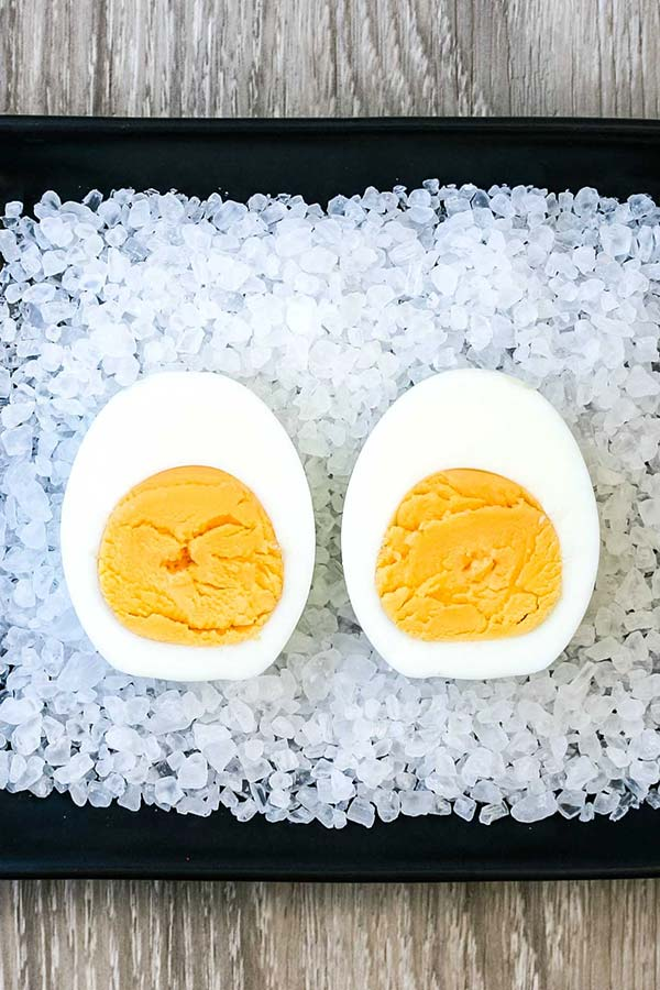A halved boiled egg, with a fully cooked yolk, on a bed of rock salt on a black serving dish