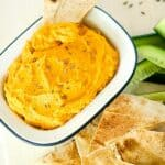 An enamel dish with carrot hummus with tortilla chips and cucumber strips.