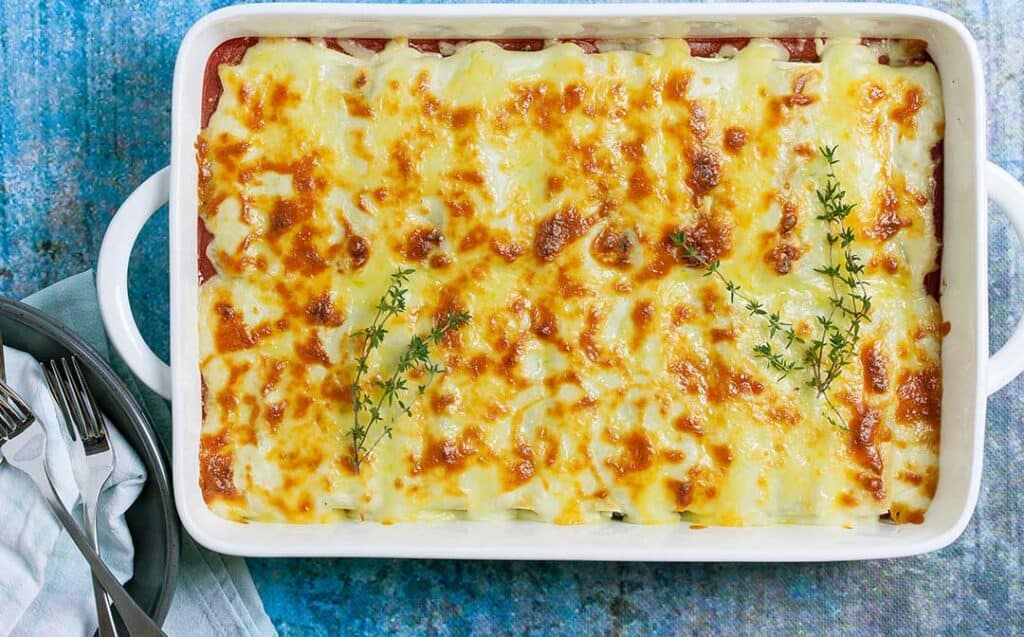 A white, rectangular casserole dish with cheesy topped baked cannelloni garnished with sprigs of thyme