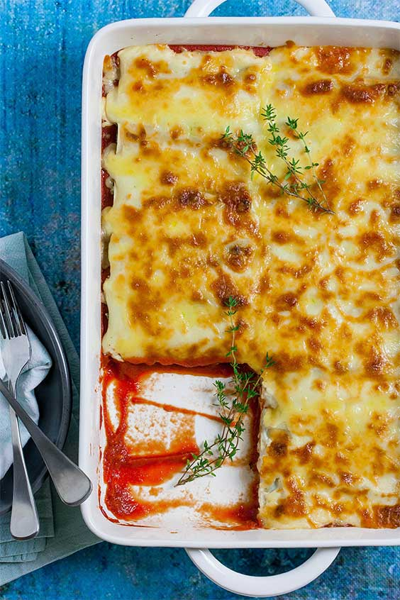 A white casserole dish with a square serving of cheesy topped baked cannelloni taken out of the dish