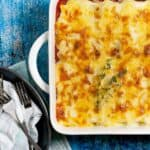 A ceramic rectangular casserole dish with spinach ricotta cannelloni garnished with sprigs of thyme