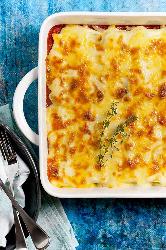 A ceramic rectangular casserole dish with cheesy topped baked cannelloni garnished with sprigs of thyme