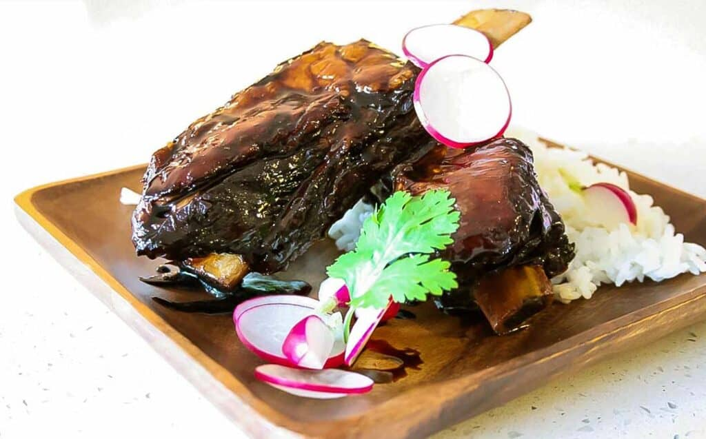 Sticky Asian Beef Ribs on a wooden plate with a serving of rice and garnishes.
