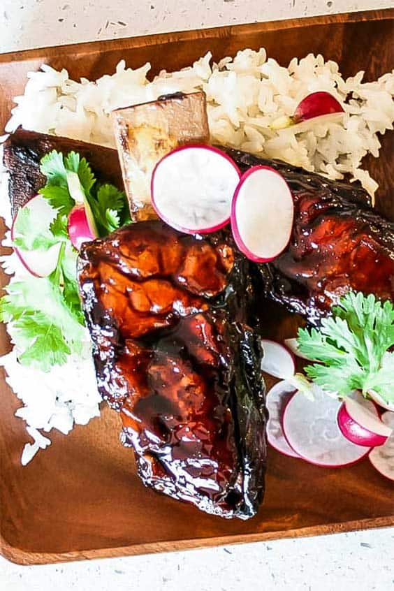 Sticky Asian Beef Ribs on a wooden plate on a bed of rice and garnished with radish and herbs