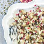 Cauliflower salad on a white scalloped edge plate garnished with mixed seeds