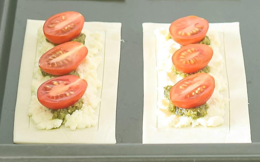 2 raw puff pastry cherry tomato tarts on a baking tray