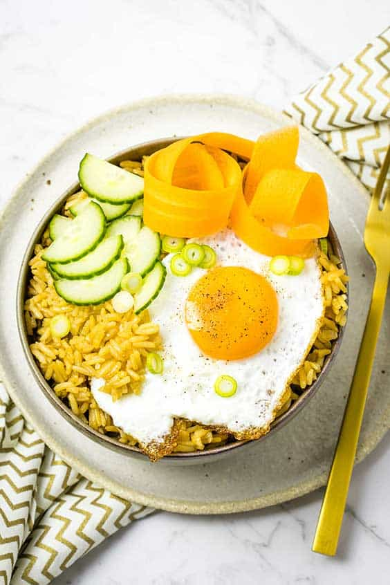 A bowl with seasoned rice topped with a fried egg, cucumber moons, pickled carrot and scallions