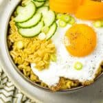 A zoomed in picture of seasoned rice topped with a seasoned fried egg, cucumber moons, pickled carrot and scallions