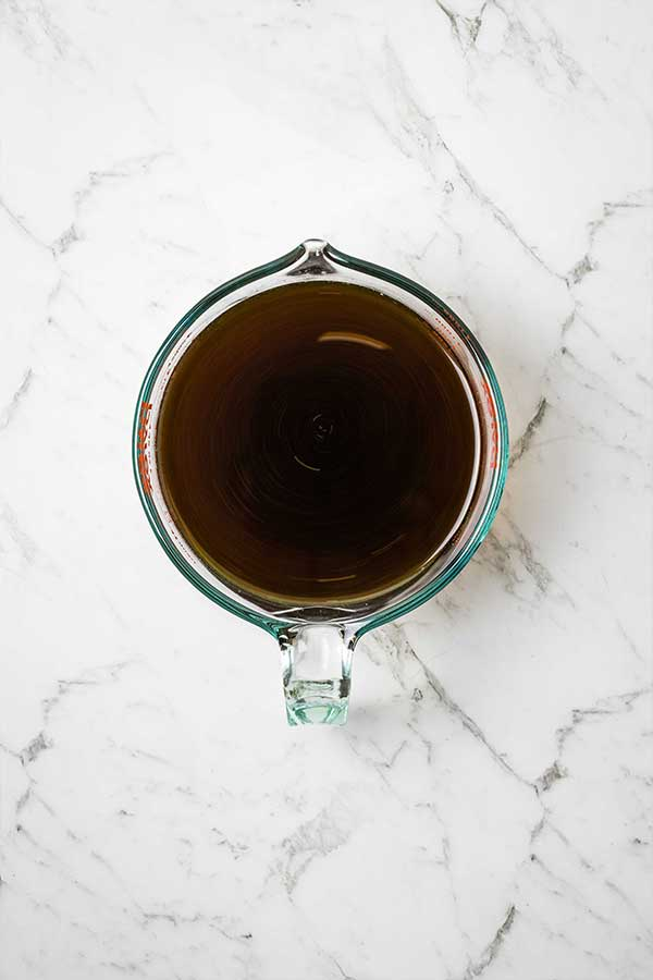 A glass jug with a dark liquid on a marble countertop