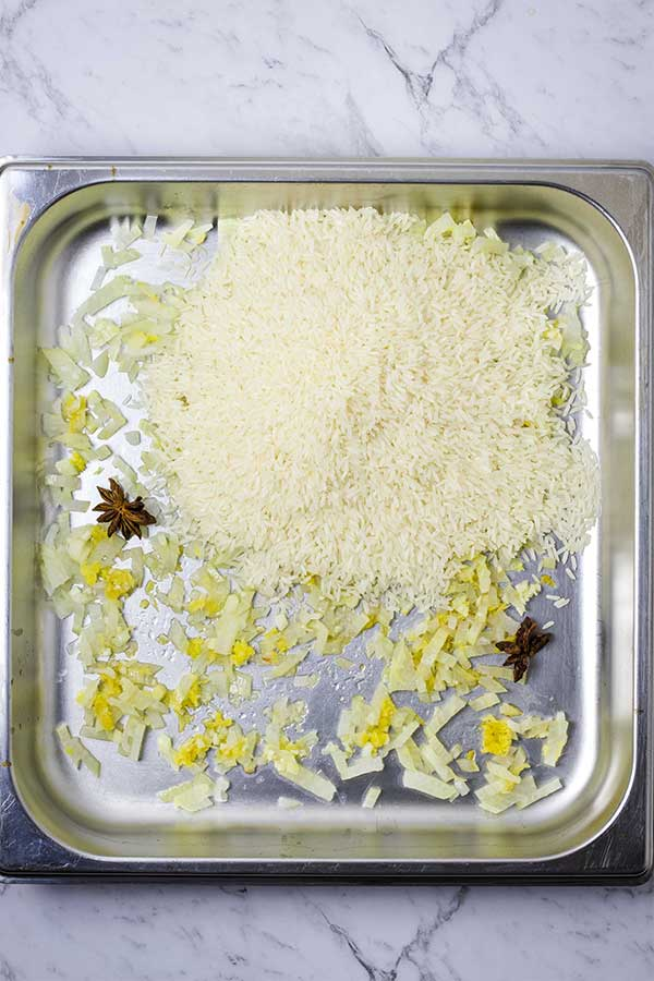 Raw rice added to a stainless steel pan with roasted onions, garlic, ginger and star anise