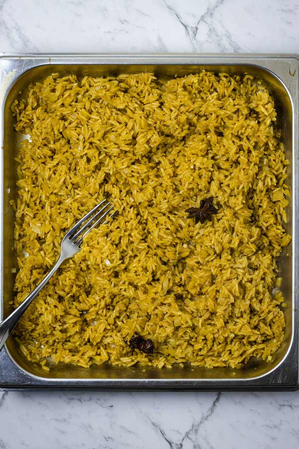 Rice being fluffed with a fork in a stainless steel pan
