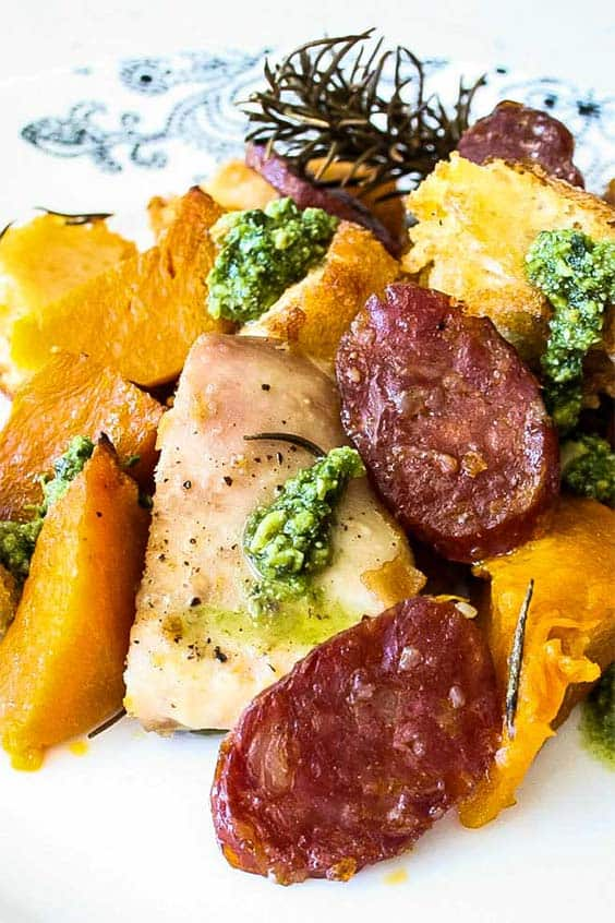Chorizo Pumpkin and Chicken Tray Bake served on a patterned plate, with rosemary and green pesto garnish.