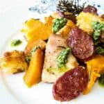 Pieces of Chorizo Pumpkin and Chicken Tray Bake served on a patterned plate, with rosemary and green pesto garnish.