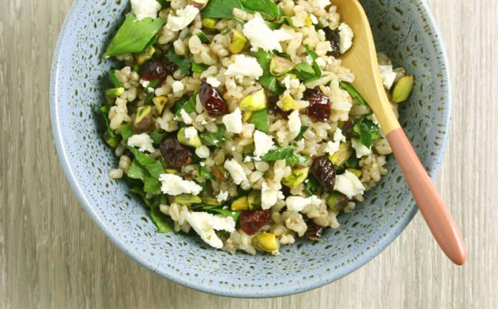 A speckled blue bowl with a rice salad with cranberries, pistachios, feta and fresh herbs and a salad server