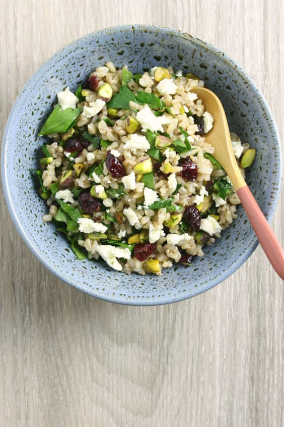 A speckled blue bowl on a pale wooden board, with a rice salad with cranberries, pistachios, feta and fresh herbs and a salad server.