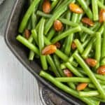 The corner of a baking tin with vibrant, glossy green beans and almonds