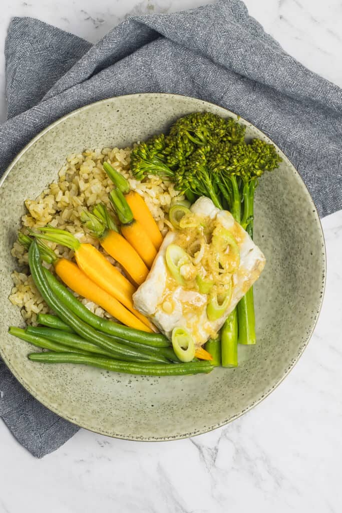 A zoomed out picture of a grey speckled plate with steamed fish and mixed veg