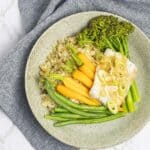 A speckled plate with steamed fish and vegetables on a grey linen teatowel