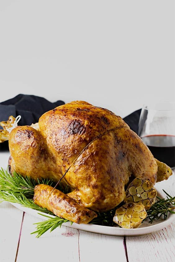 A white oval platter with a roasted turkey and a halved head of garlic resting on a bed of rosemary sprigs