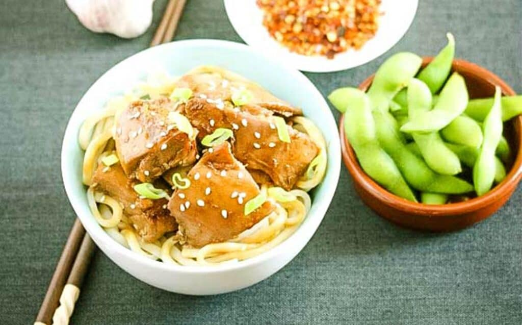 A bowl of noodles with chicken pieces and a bowl of edamame beans