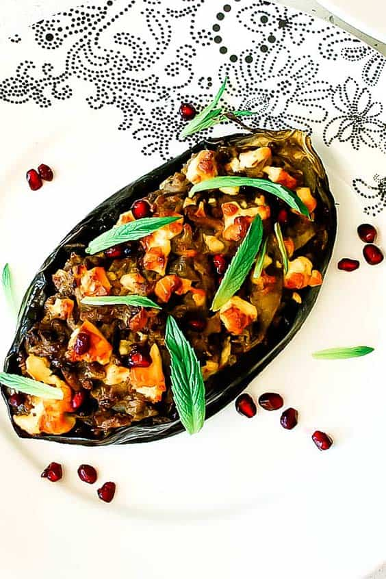 A halved eggplant stuffed with a savoury mixture and herbs on a patterned plate