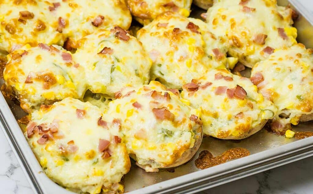 a stainless steel pan full of twice baked potatoes covered in melted cheese, bacon and scallions