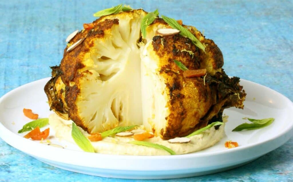 a roasted cauliflower, with a wedge cut out of it, on a white plate