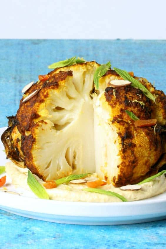 a roasted cauliflower on a bed of hummus, with a wedge cut out of it, on a white plate