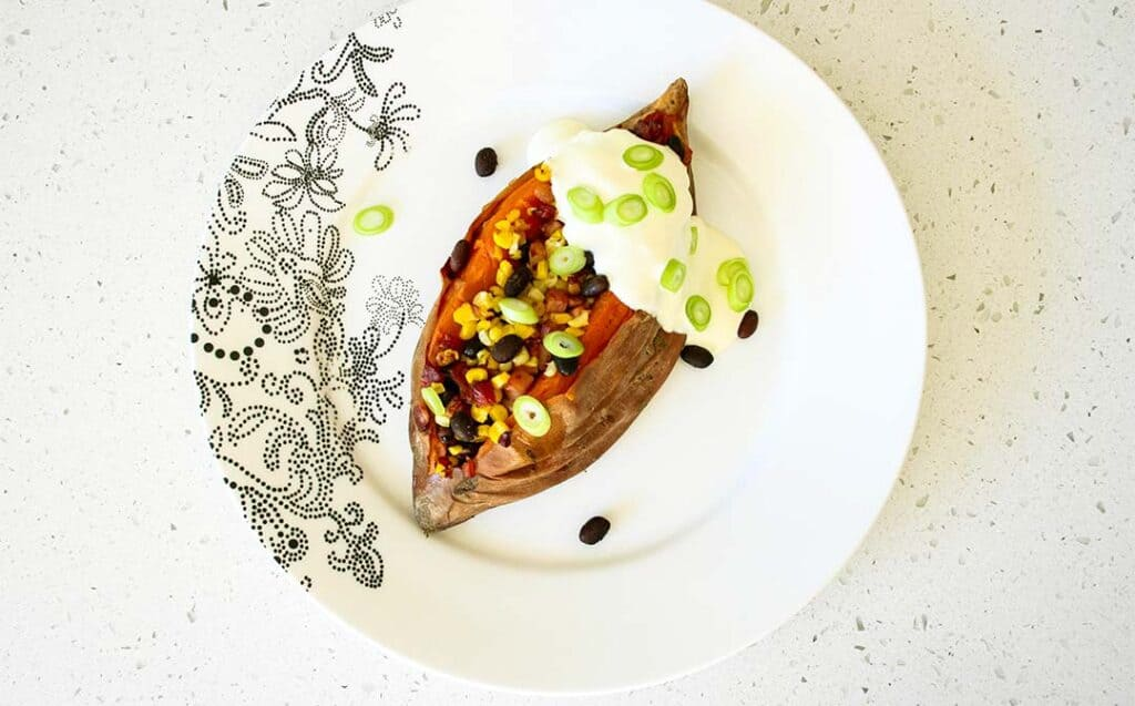 A loaded sweet potato stuffed with beans and corn, topped with sour cream garnished with sliced green onions on a patterned plate.
