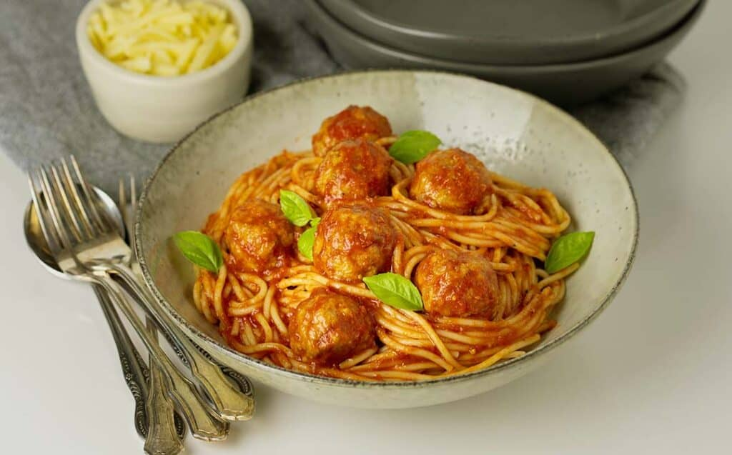 A serving bowl with saucy spaghetti and meatballs garnished with herbs