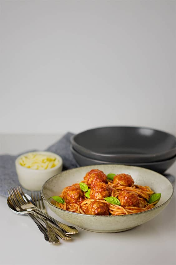 A picture of a bowl of oven baked meatballs in tomato sauce in the foreground and bowls and grated cheese in a ramekin