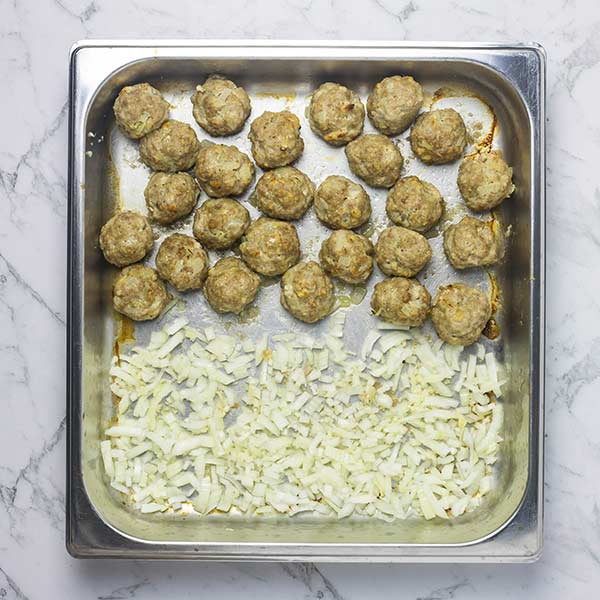 Partially browned meatballs on one side of a steel baking dish with chopped garlic and onion on the other
