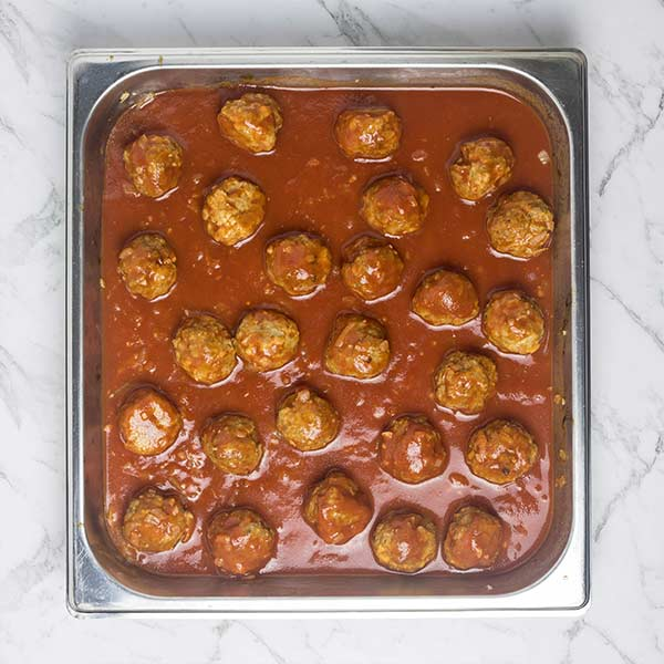 Meatballs in a tomato sauce in a steel baking dish on a marble countertop