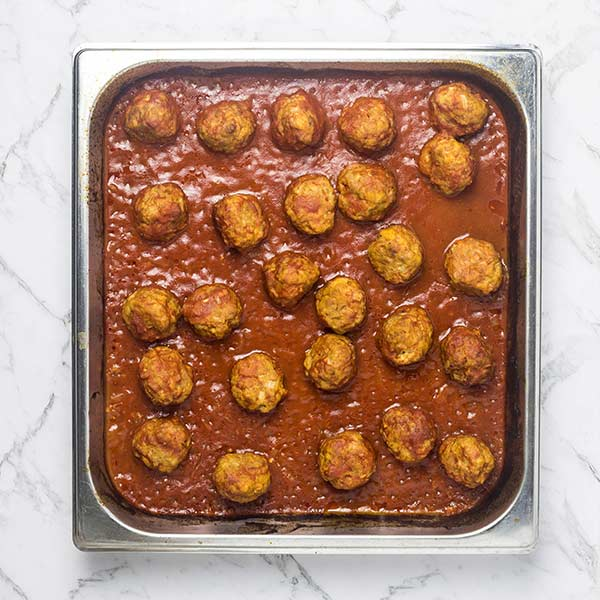 Oven baked Meatballs in a reduced tomato sauce in a steel baking dish on a marble countertop