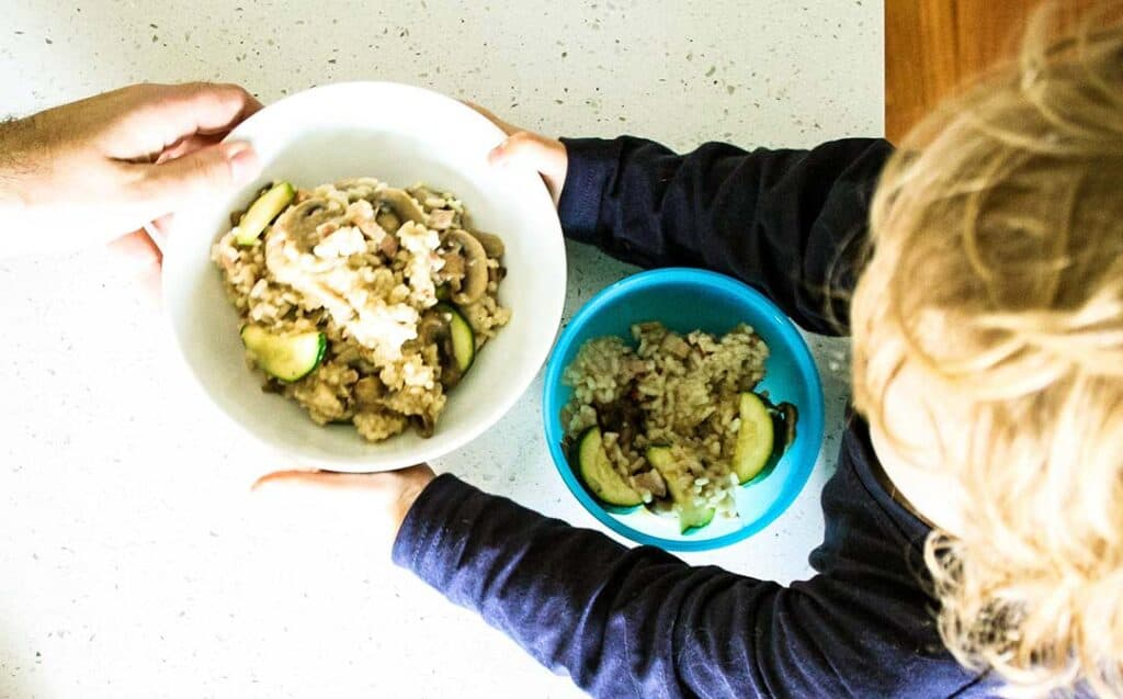 child holding risotto bowl