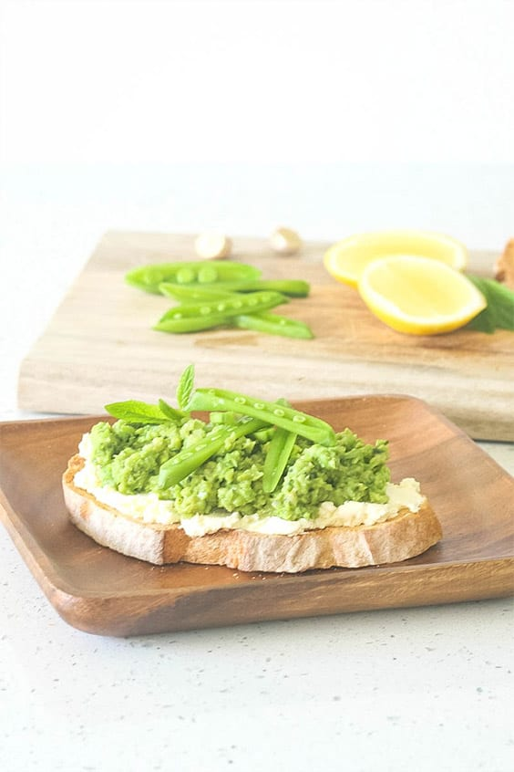 Smashed Pea and Fava Bean Crostini on a wooden plate