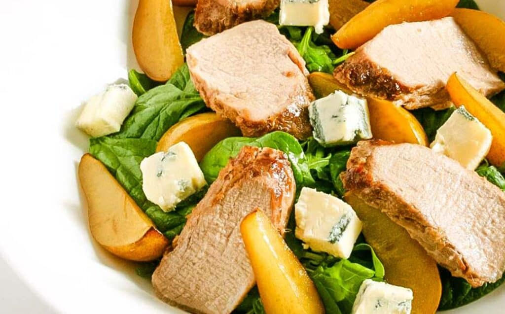 A white bowl with a salad of roasted pork and slices of pear with salad greens and gorgonzola cheese chunks