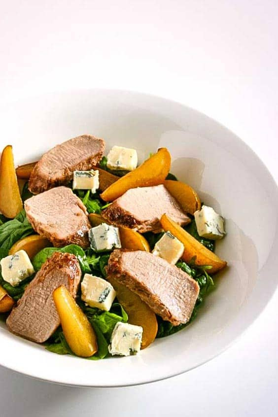 A white bowl with pieces of roasted pork and slices of pear with salad greens and gorgonzola cheese