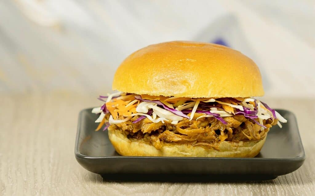 A burger bun with pulled pork and coleslaw on a curved black plate on a light wood counter