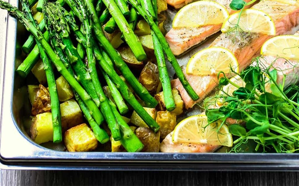 Steam oven salmon in a stainless steel roasting dish with slices of lemon, asparagus, roast potatoes and pea shoots.