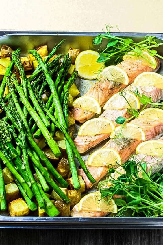 Stainless steel roasting dish with steam oven salmon, lemon slices, asparagus, roast potatoes and pea shoots.