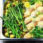 Steel roasting dish with steam oven salmon, lemon slices, asparagus, roast potatoes and pea shoots.