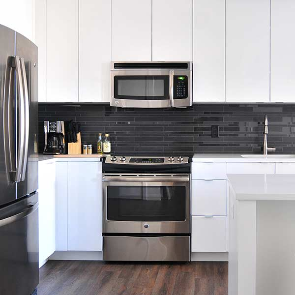 A kitchen with white benches and a large steam oven and range with a microwave above it