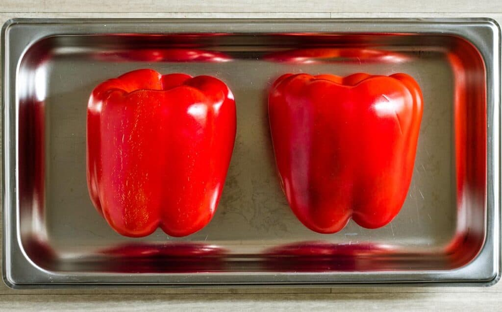 A silver baking tray with two whole peppers