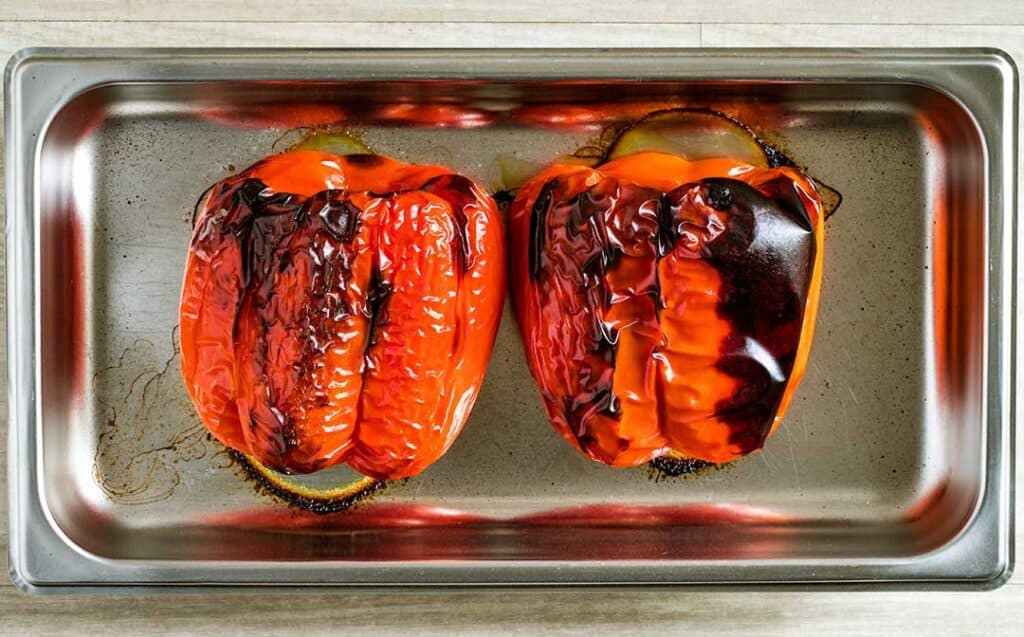 A silver baking tray with two whole roasted peppers